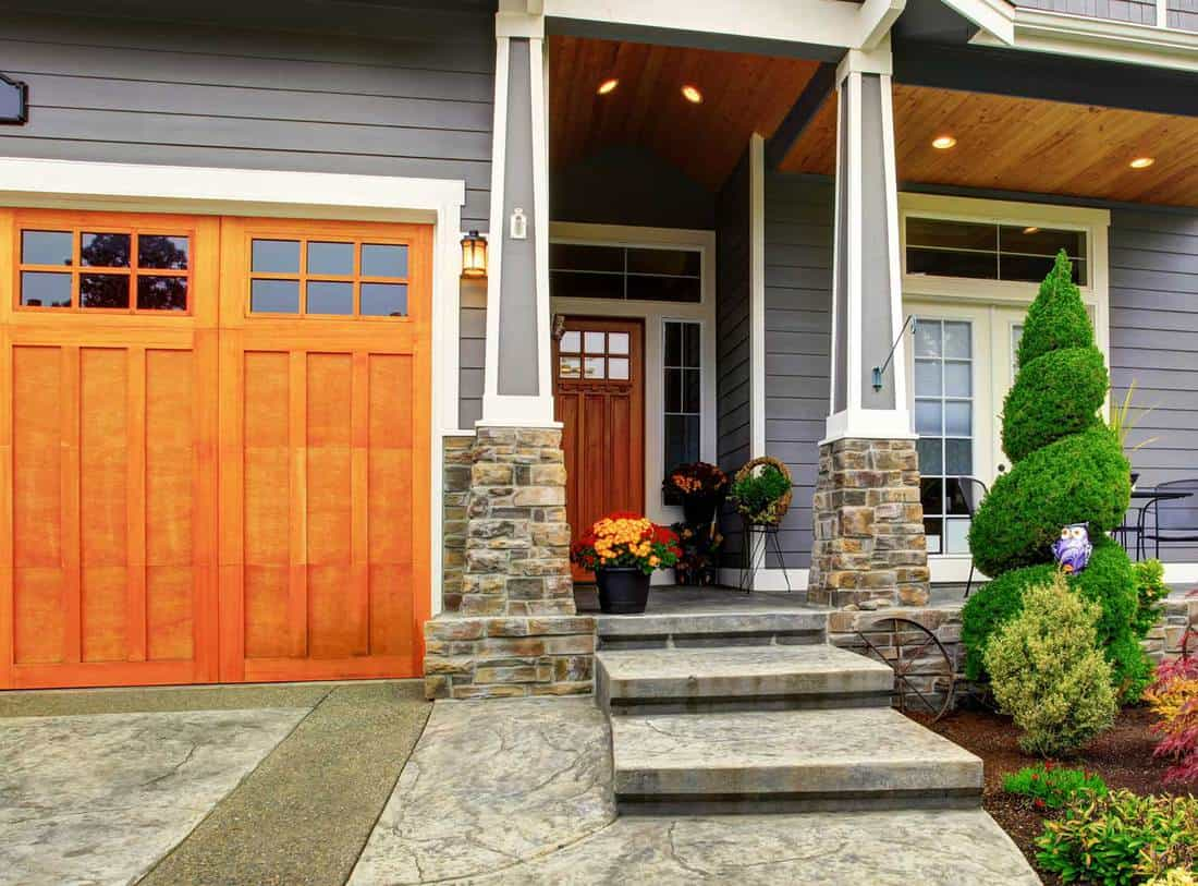 Luxury house entrance porch with stone column trim and wooden door
