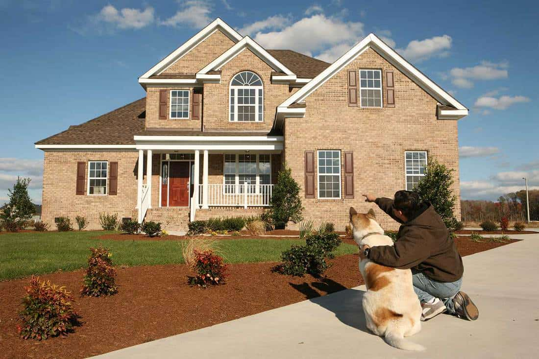 Man showing his dog their new home with brick walls and red door