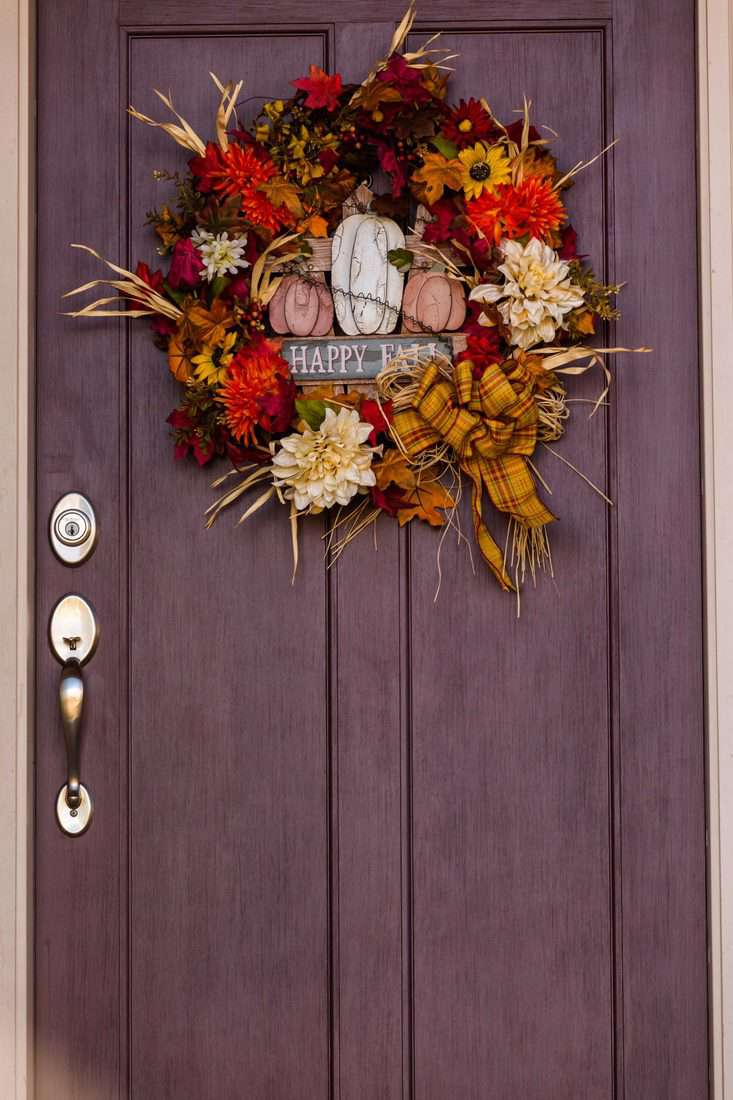 Maple door with wreath made with flowers and withered leaves