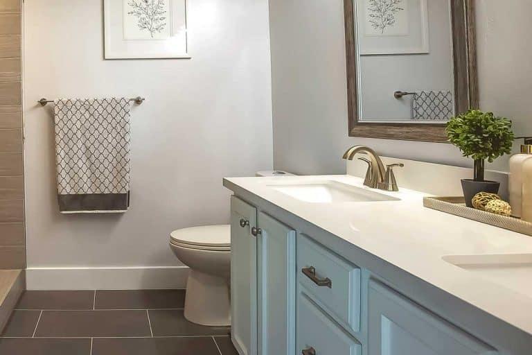 Modern bathroom with double sink vanity, toilet, towel and mirror