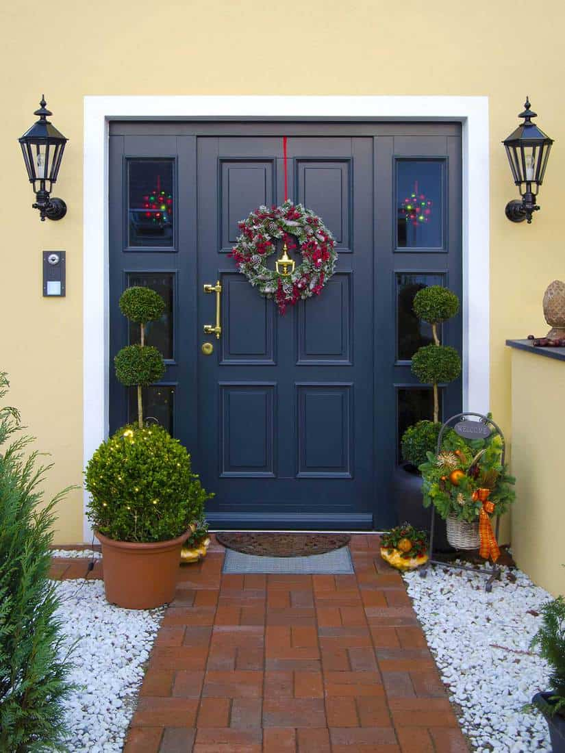 Modern dark blue wooden front door decorated with garland