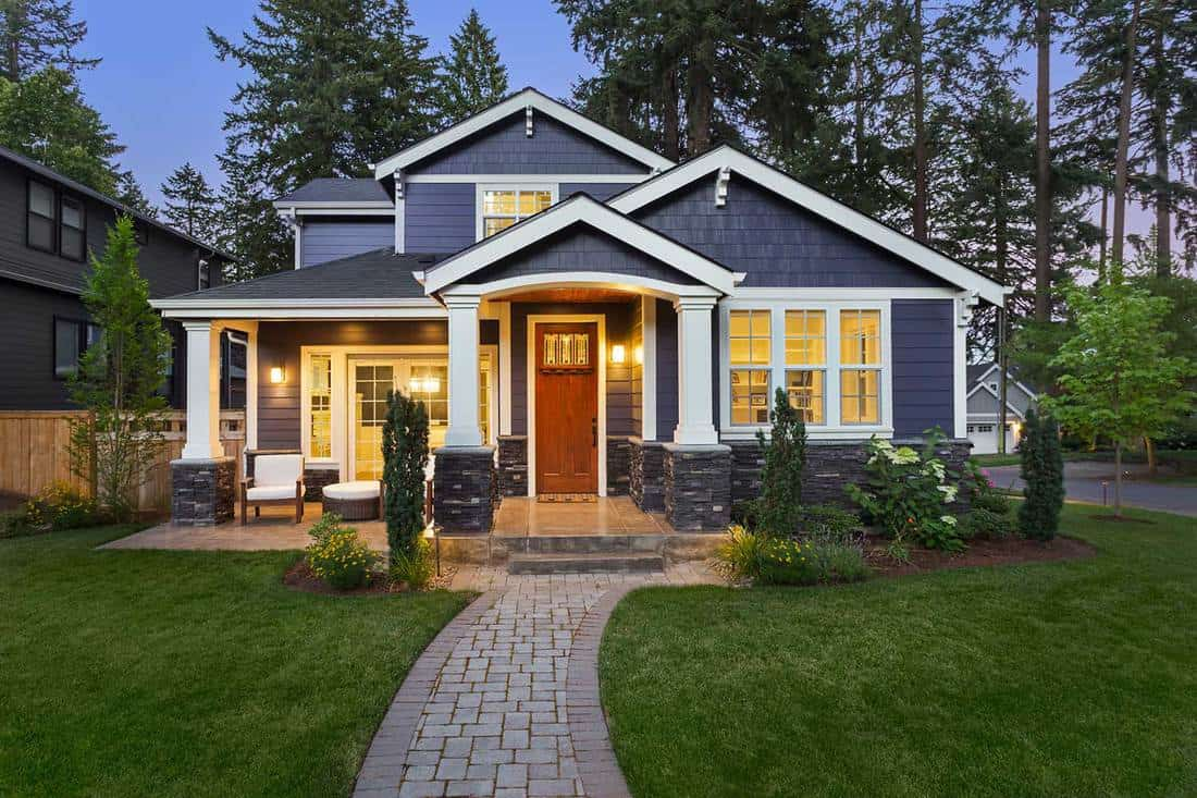 Modern home exterior with walkway to front porch and manicured lawn
