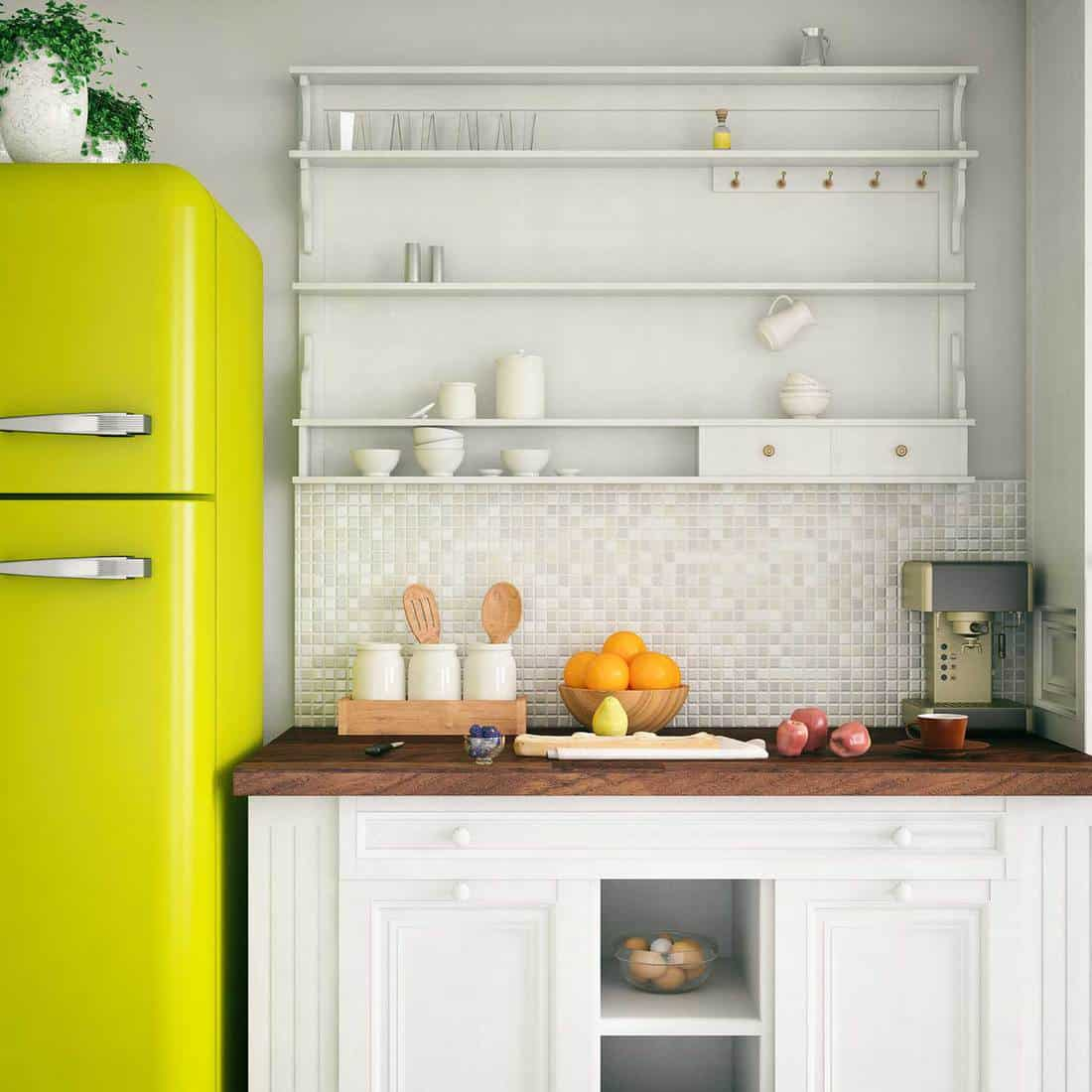Modern house kitchen with yellow fridge, wooden countertop and bowl of oranges