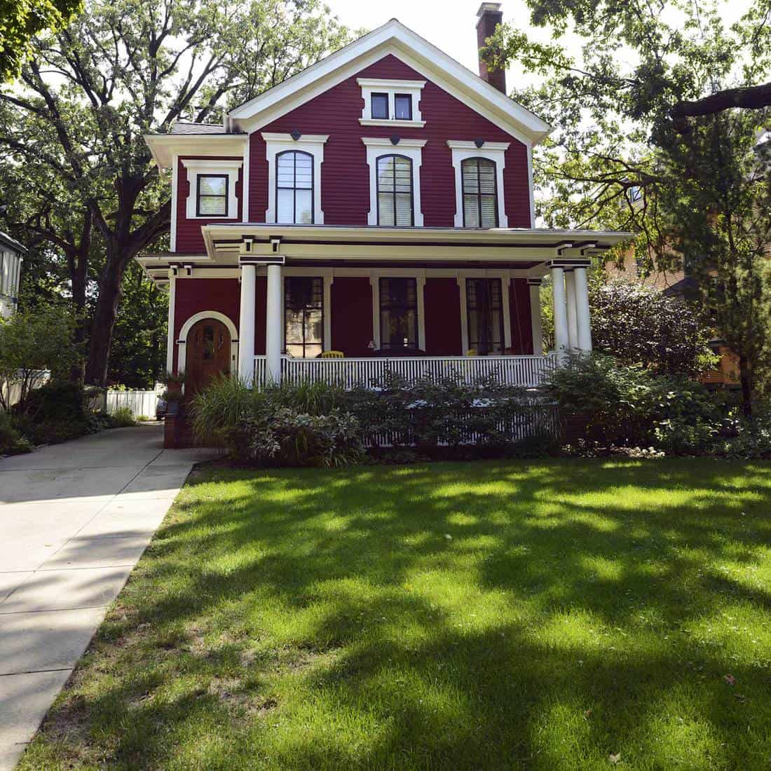 Modern maroon house with front porch and lawn