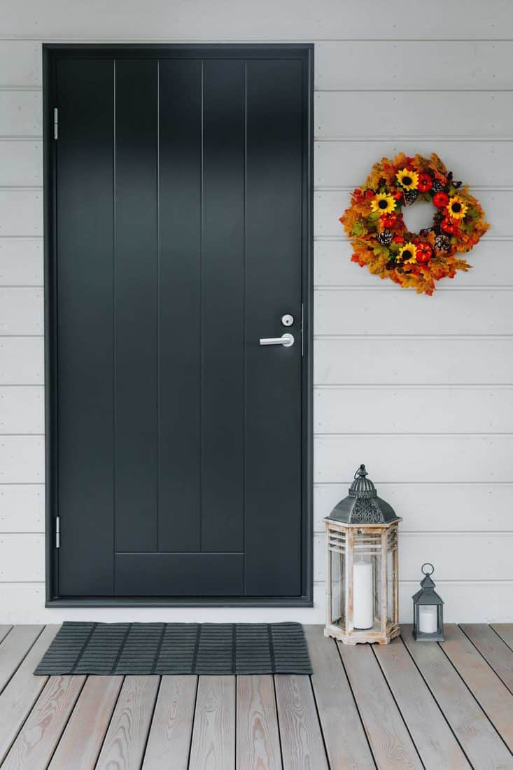 Modern themed entrance with dark grey aluminum door and fall themed decorative wreath