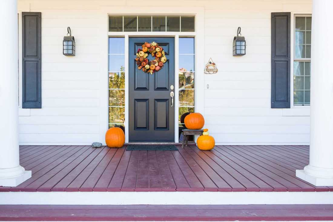 Modern themed facade with themed wreath and pumpkins place at wooden deck flooring