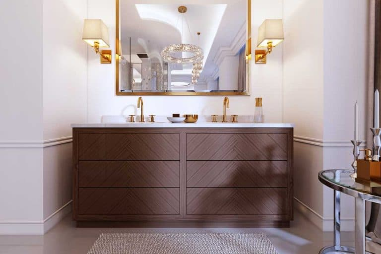 Modern wooden vanity with a mirror in a gold frame and sconces on the wall