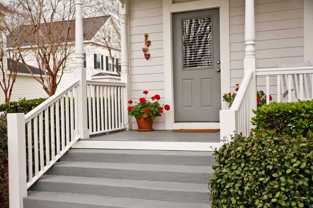 Neutral white colored porch with stairs and grey door with window