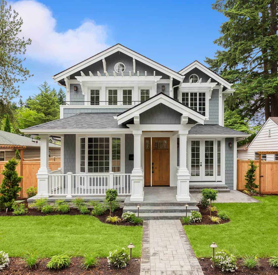 New luxury home with elegant touches including covered entrance and manicured lawn