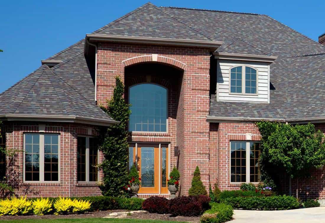 New red brick home exterior with honey yellow front door