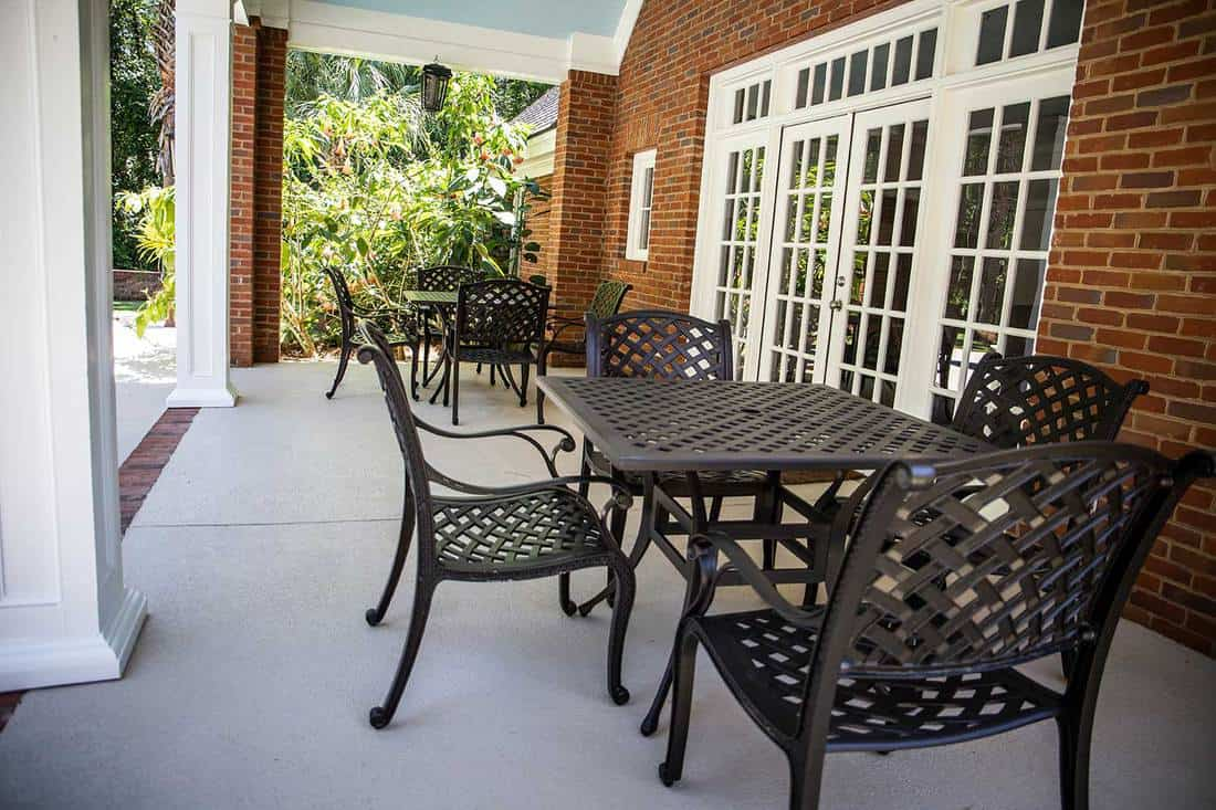 Outdoor red brick porch patio of a modern house with black iron chairs and tables for outdoor barbeques and glass double doors