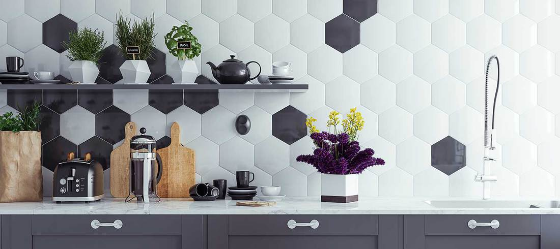 Panoramic view of a modern kitchen with hexagon shaped tiles on wall, coffee maker, toaster and kitchen utensils