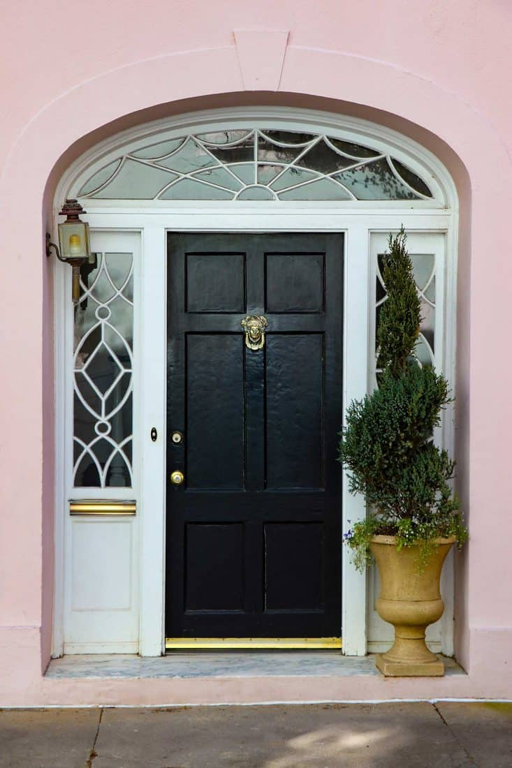 Pink wall and arched door way with black door and window sidings