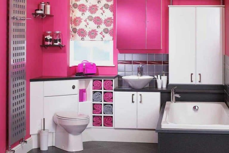 Pink wall bathroom with tiled floor, bathtub, toilet and towels on cabinets