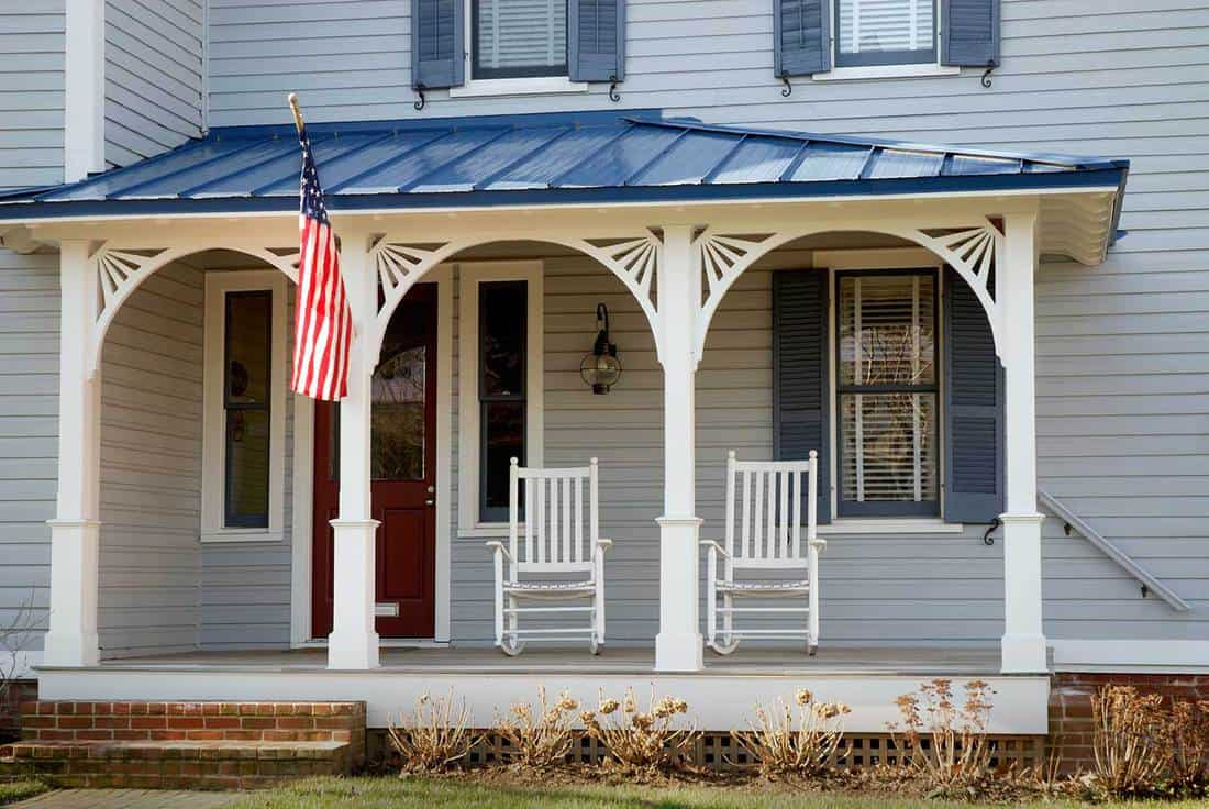 Porch of a blue house with American flag and two white wooden rocking chairs