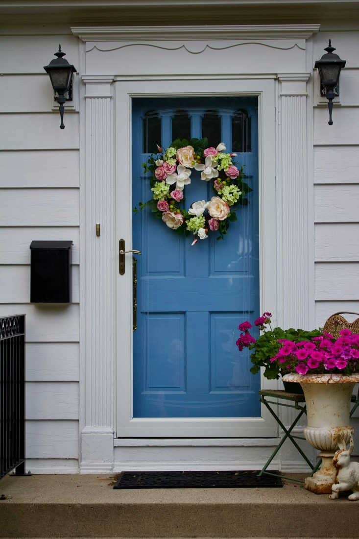 Porch with industrial themed lamps and blue door with flower wreath