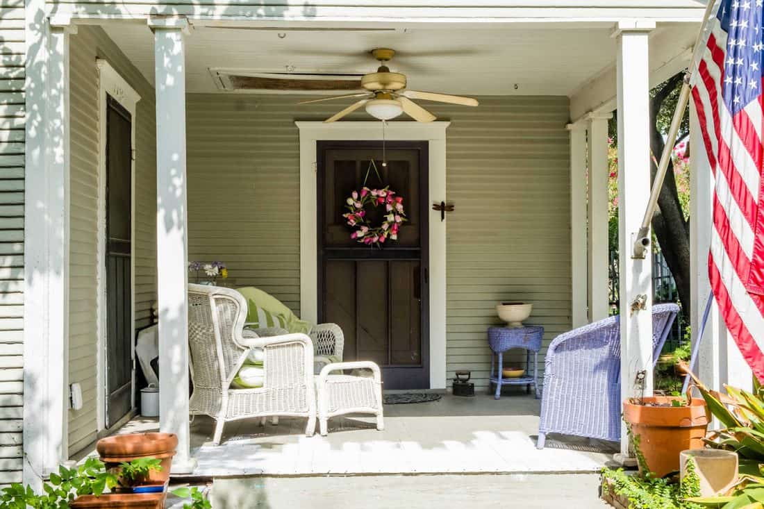 Porch with light brown colored walls and brown door with ceiling fan and chairs and the American flag at the side