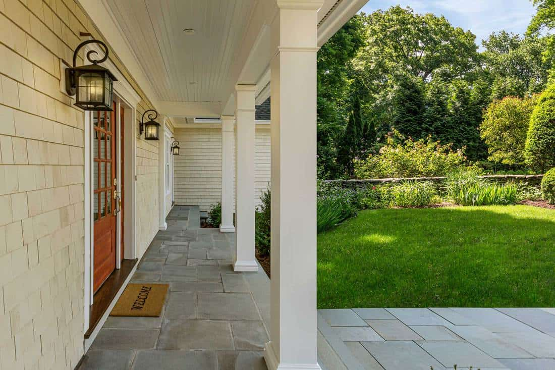 Porch with white square columns and brown door with windows