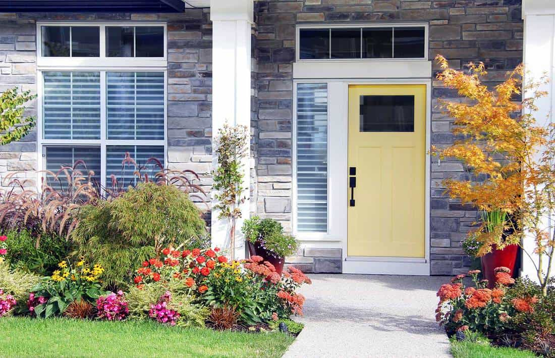 Pretty new home with a yellow front door and perennial garden