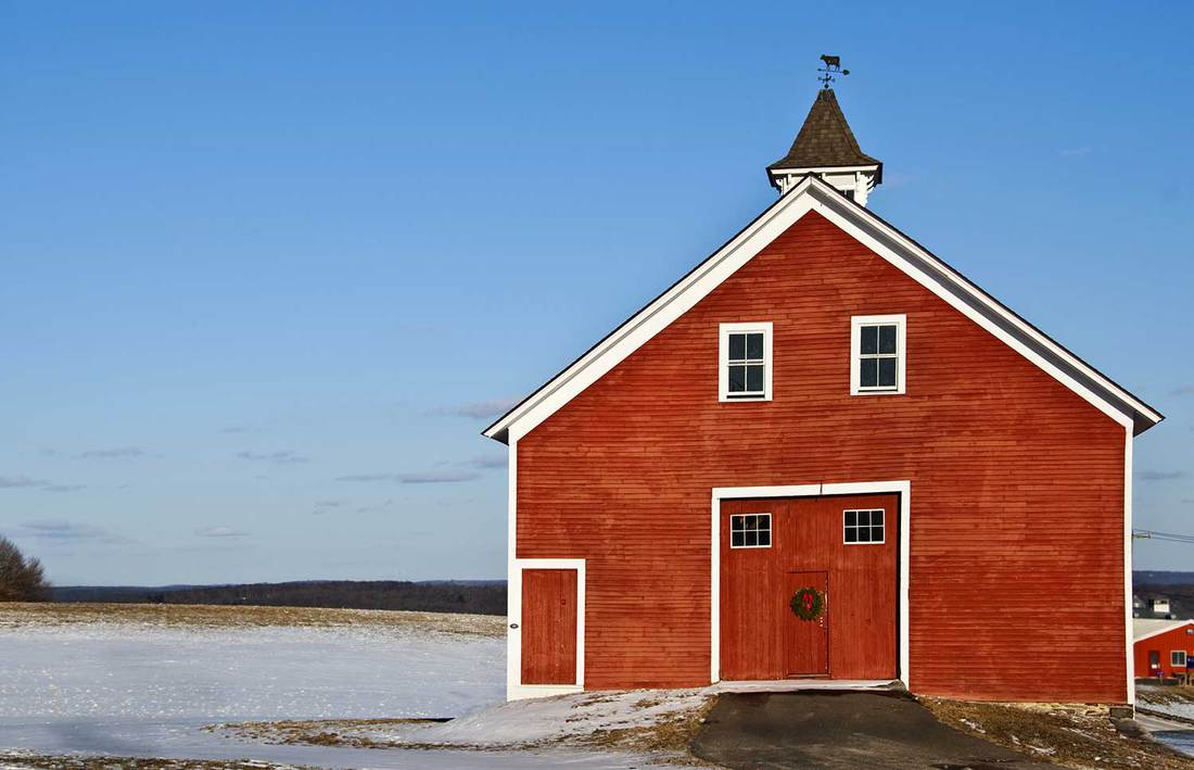 Red dairy barn with wreath on double doors