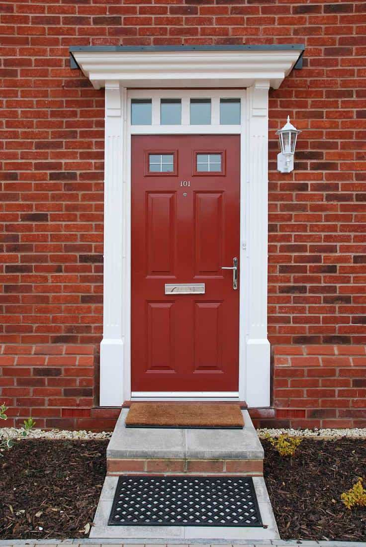 Red door entrance of a typical british residential brick house