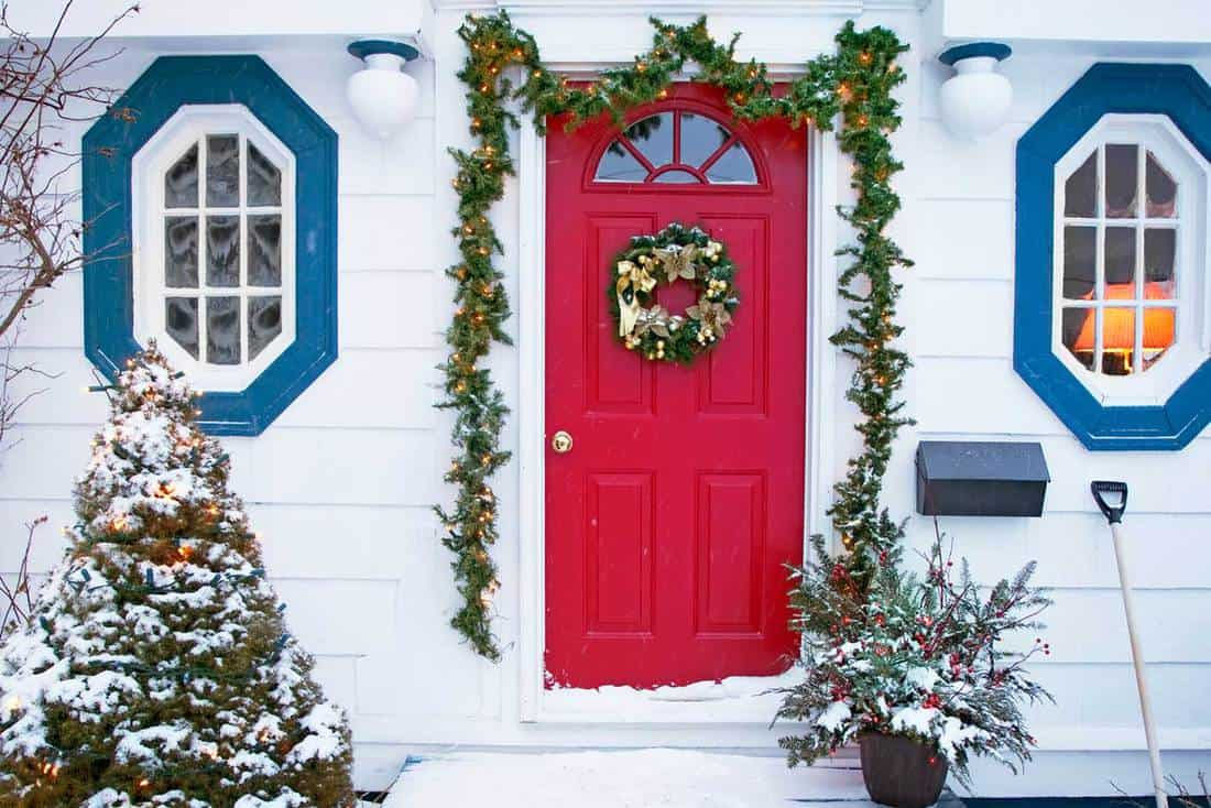 Red door with arched window attached golden decorative plastic flower