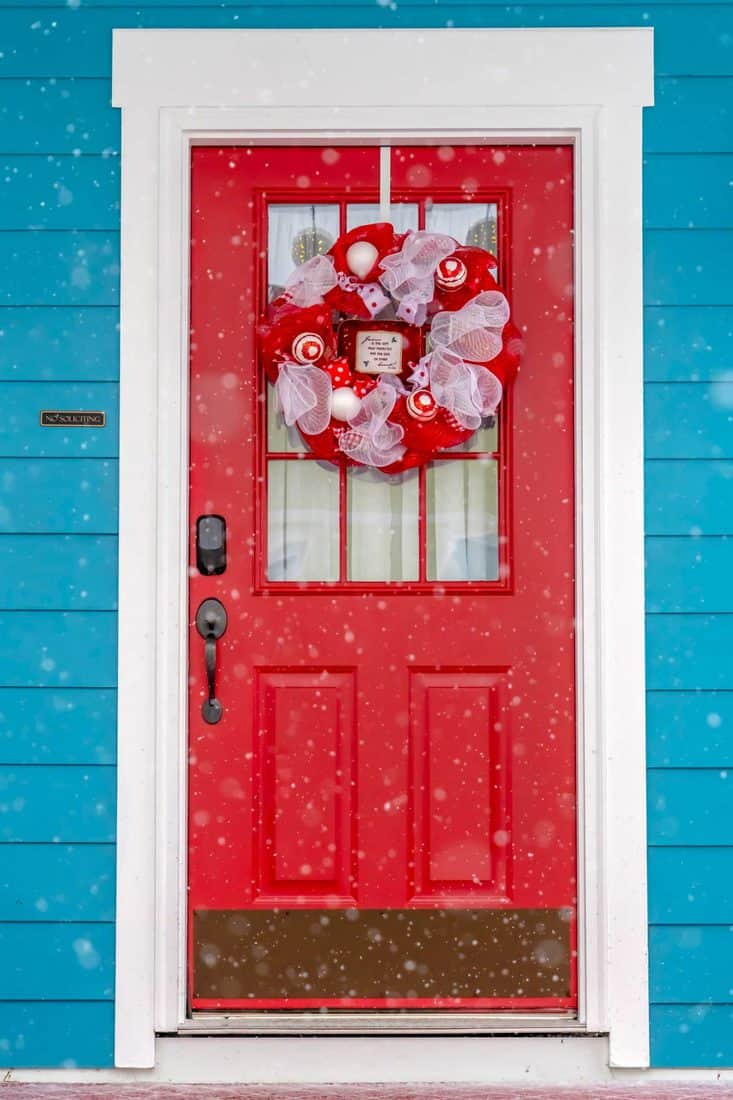 Red door with glass window attached with red decorative christmas wreath