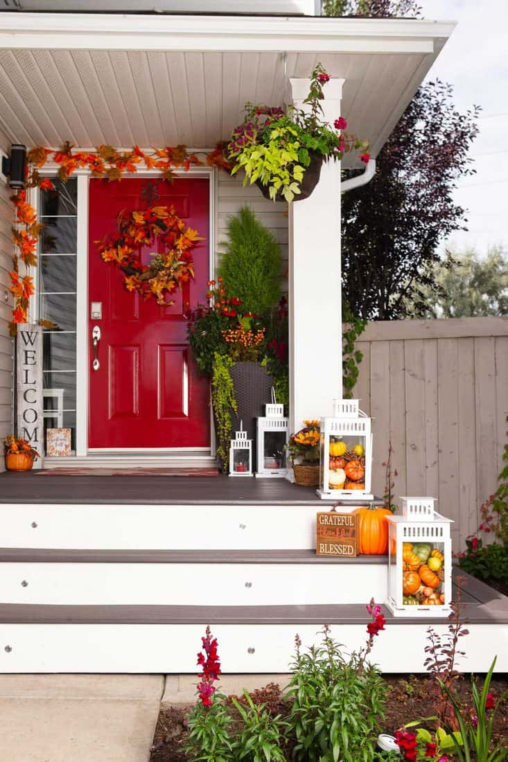 Red door with jack'o lantern at stairs and fall themed wreath