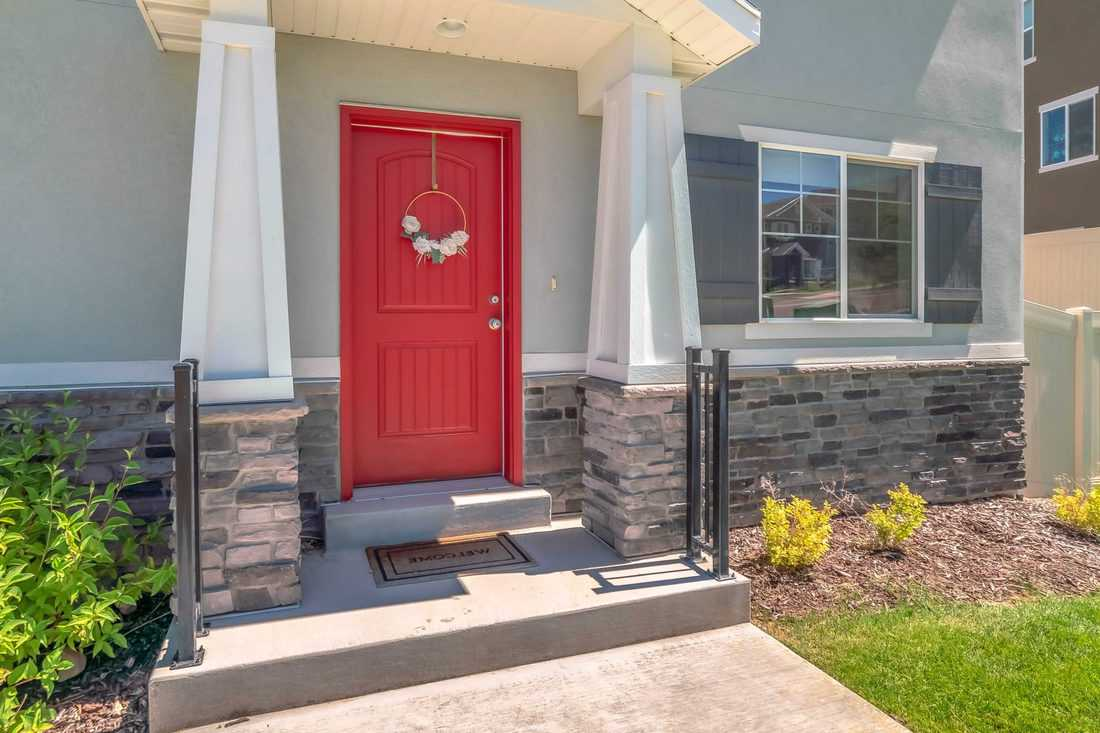 Red door with triangular shaped columns designed with decorative stones below