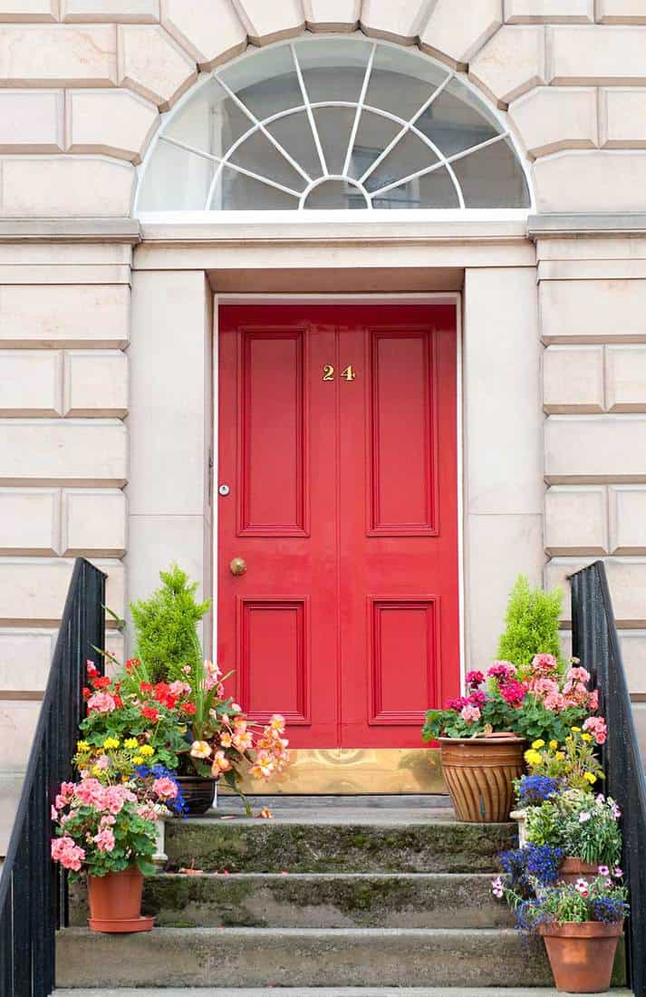 Red front door entrance with decorating flowers