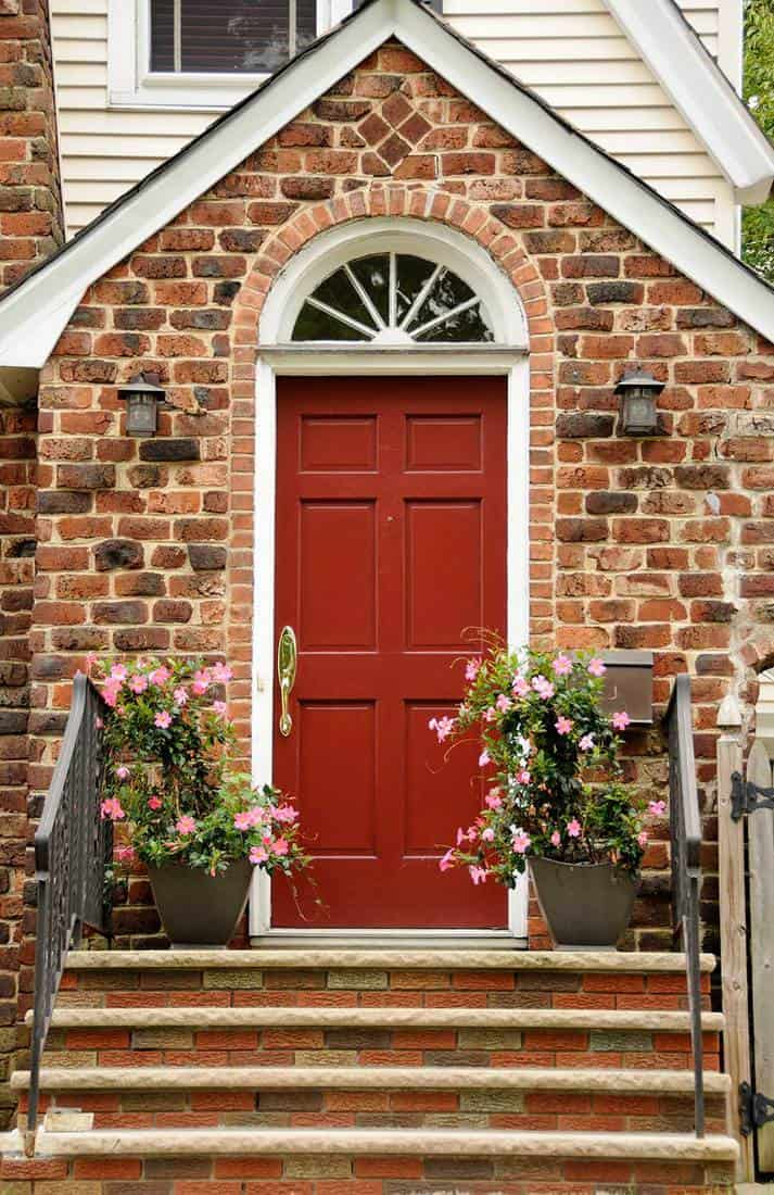 Red front door of colonial red brick home