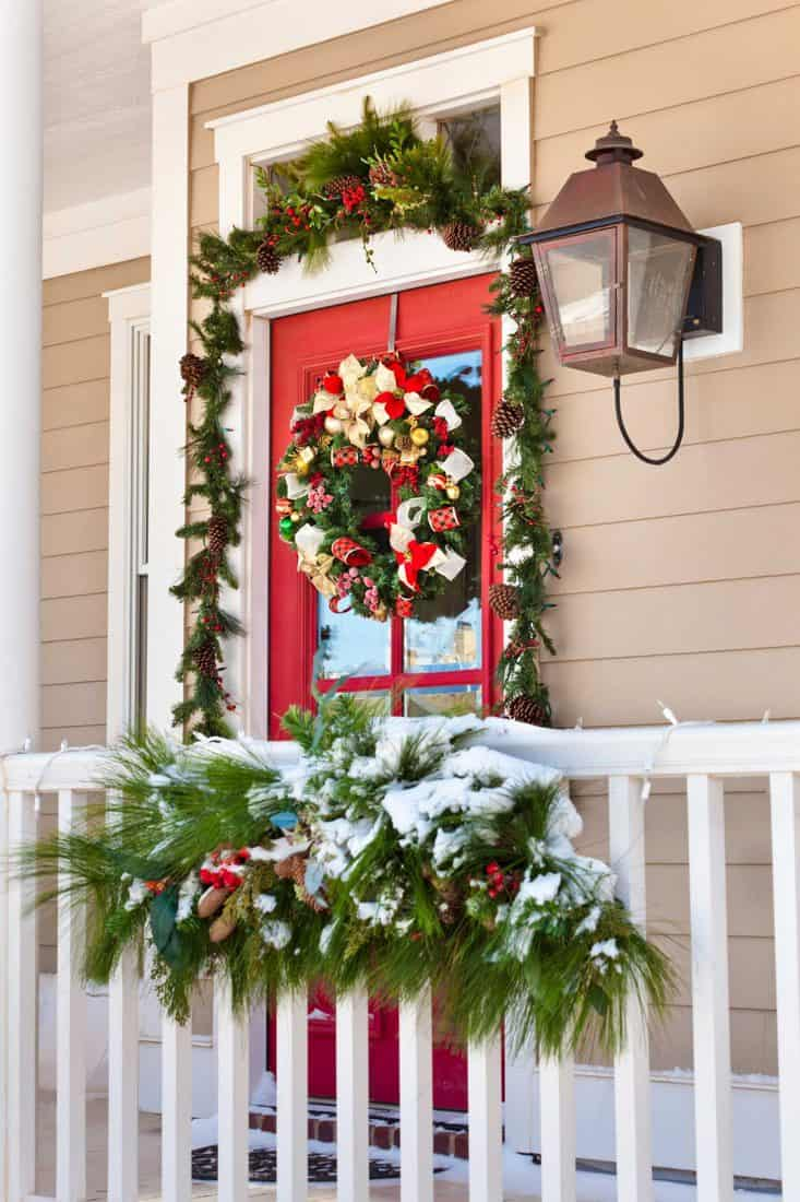Red front door with window and decorative wreath for christmas