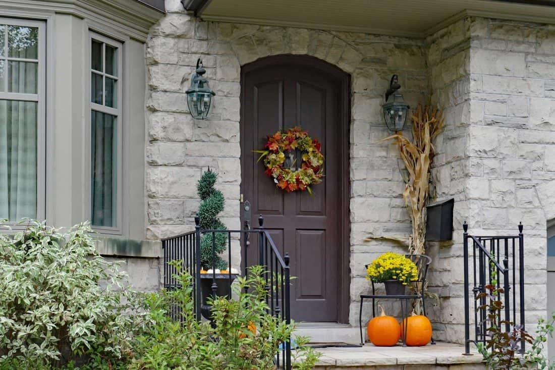 Rock designed facade with brown door with flower wreath