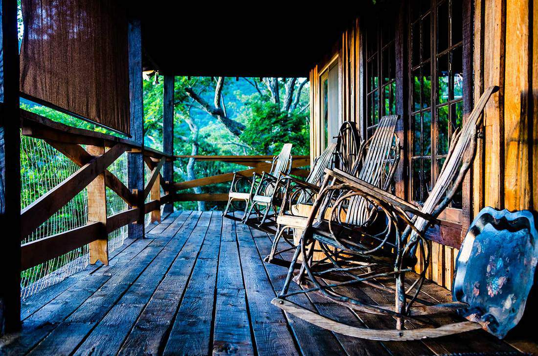 Rustic cabin porch at sunset with rocking chairs