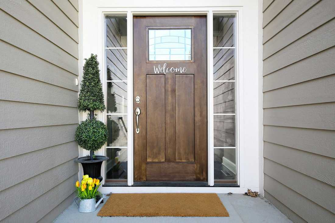 Rustic themed door with welcome sign and tree plant on pot