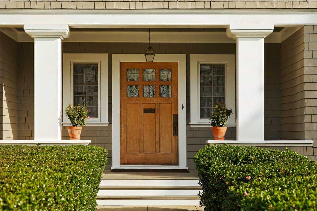 Rustic themed porch and huge main door with white colored framing