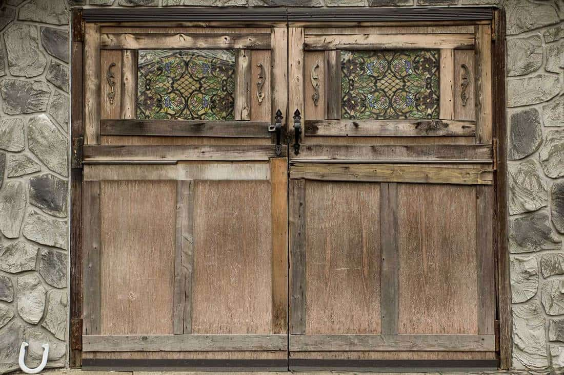 Rustic wooden barn door with lovely stained glass surrounded by stone walls