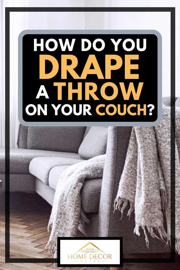 Scandinavian interior of living room with throw drape on sofa and parquet floor