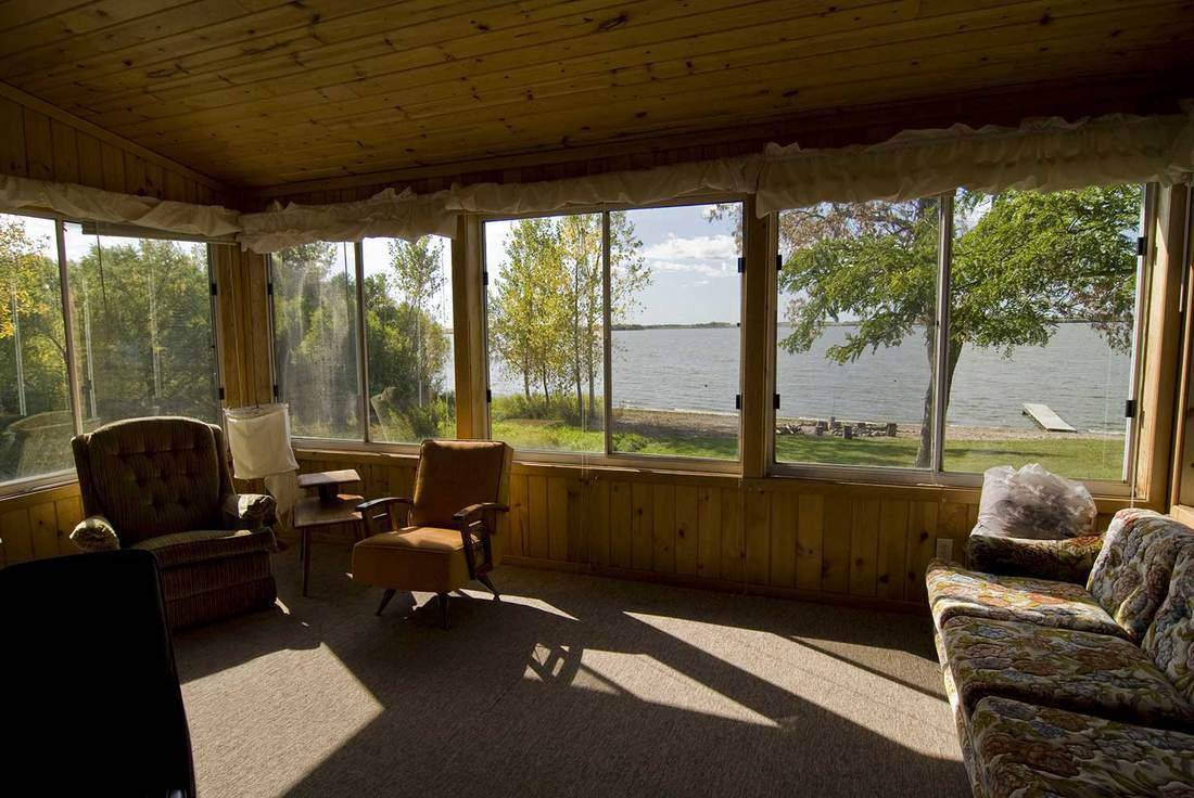 Screened in porch of a beach house overlooking lake and trees on a sunny day with strong shadows