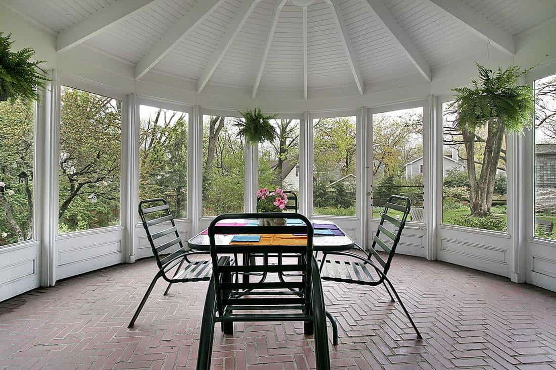 Screened in porch with table and brick floor and house plants