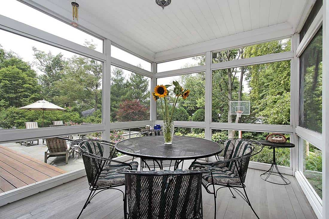 Screened in porch with table and wood floor overlooking patio and basketball court