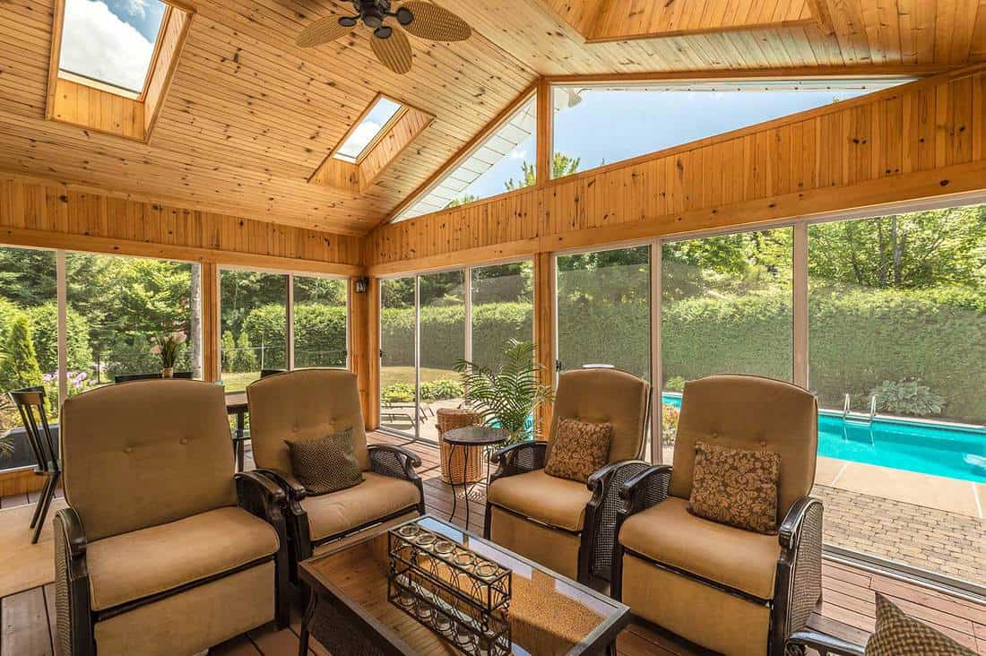 Screened in wooden porch overlooking backyard pool