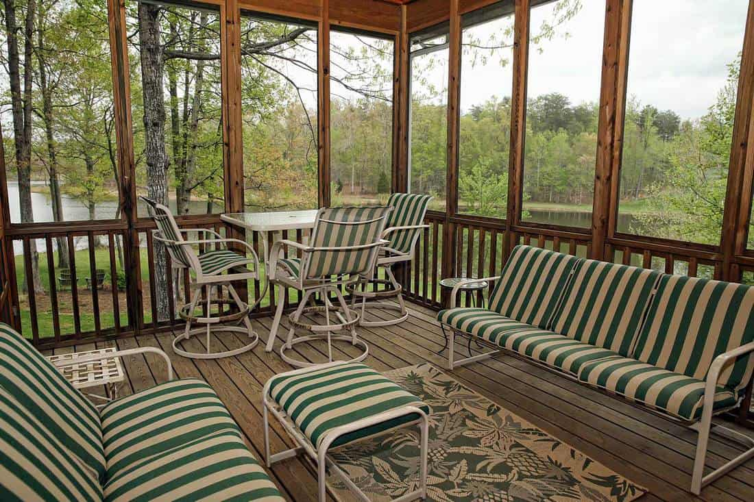 Screened porch on lakeside property with chairs striped with green