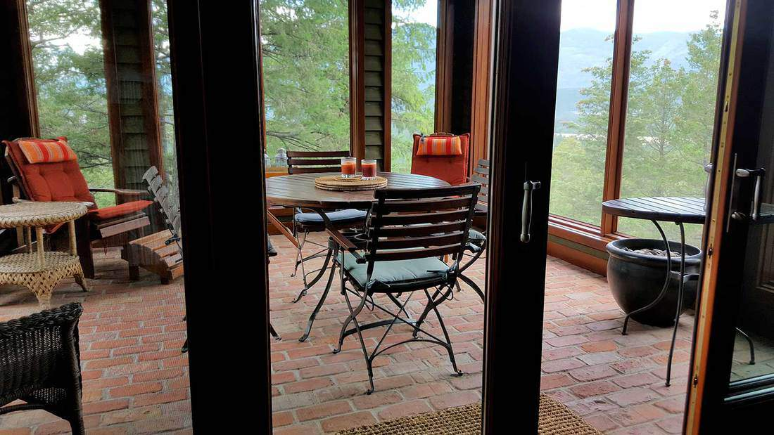 Screened porch with vintage brick floor, wicker furniture and adirondack chairs surrounded by trees