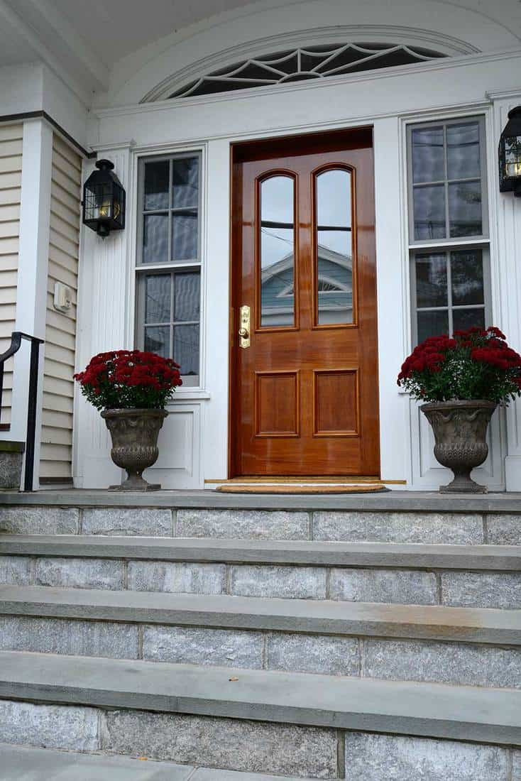 Slate steps leading up to a fancy wood door for a federal style house with flowers in planters
