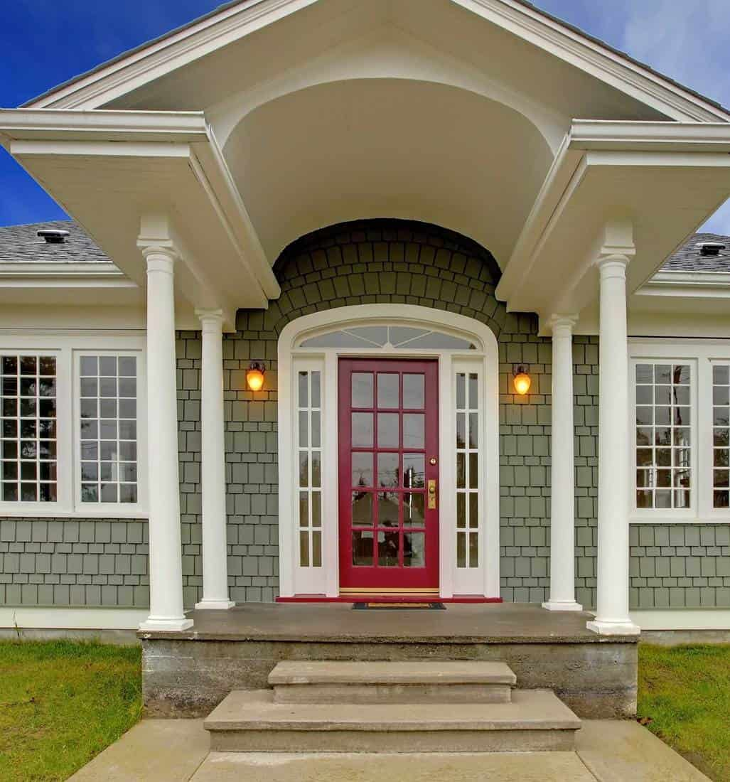 Small cute grey New England style home with pink red door