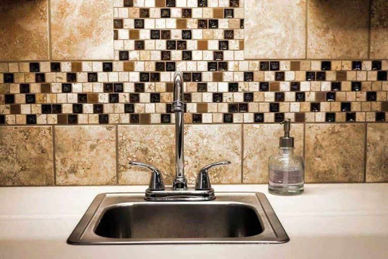 Small sink with faucet with brown mosaic tile backsplash