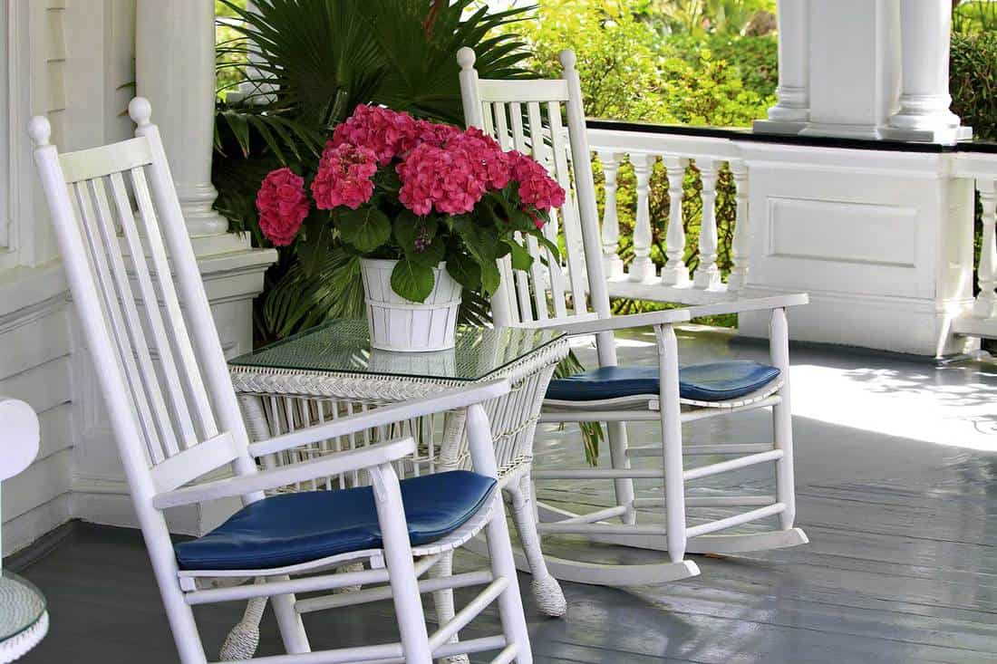 Southern porch with two white rocking chairs and flowers