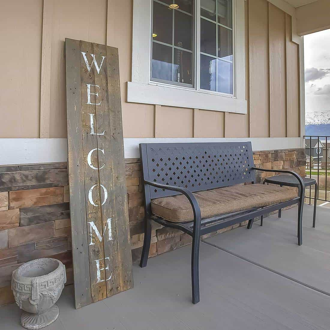 Square wooden welcome sign and furniture on the front porch of a residence with exterior wall made of wooden and stone brick section