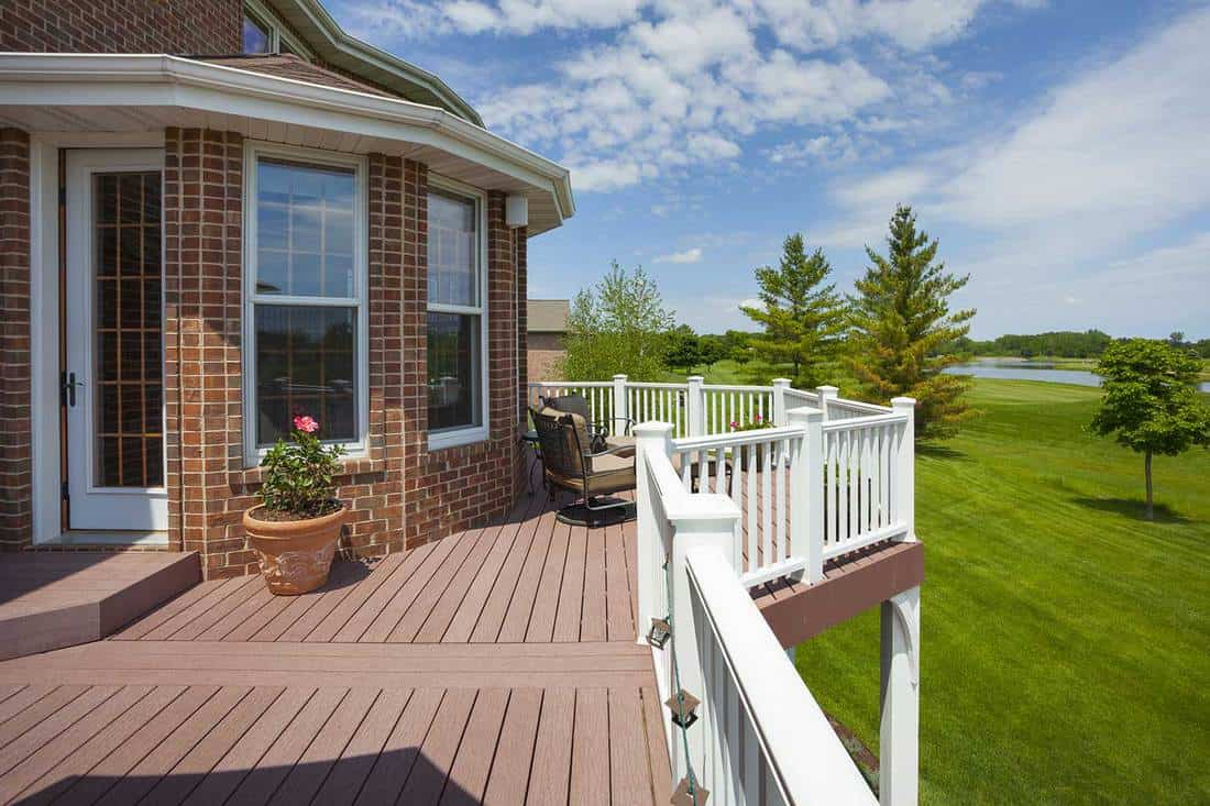Stunning home deck with red brick walls and view of golf course